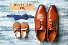 Grandes et petites chaussures de noeud papillon, sur le fond en bois Image libre de droits