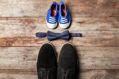 Grandes et petites chaussures de noeud papillon, sur le fond en bois Images stock