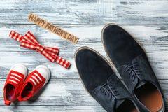 Grandes et petites chaussures de noeud papillon, sur le fond en bois Photos stock