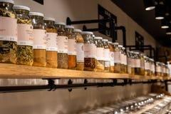 Grandes frascos de vidro das especiarias e dos alimentos inteiros alinhados em prateleiras em uma loja fotos de stock