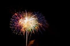 Grandes fuegos artificiales sobre una ciudad por noche imagen de archivo