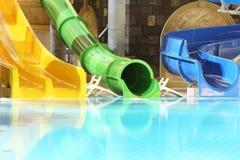 Grandes glissières et piscine d'eau dans l'aquapark d'intérieur photographie stock
