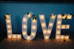 Grandes lettres d'amour rougeoyantes avec les ampoules Images stock