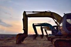 Grandes máquinas escavadoras no fulgor do por do sol do nascer do sol da expressão artística Imagens de Stock