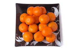 Grandes mandarines mûres dans un plat en verre sur un fond blanc. Photos stock