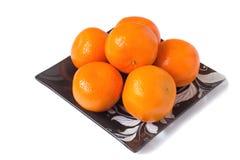 Grandes mandarines mûres dans un plat en verre sur un fond blanc. Image libre de droits
