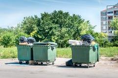 Grandes nouvelles poubelles en plastique de décharge complètement des ordures de débordement polluant la rue dans la ville avec l image libre de droits