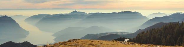 Grandes paisagem no lago Iseo na estação do inverno, nevoento e na umidade no ar Panorama de Monte Pora, cumes, Itália fotografia de stock