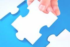 Grandes partes do enigma de serra de vaivém na mesa azul fotos de stock