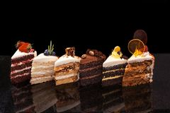 Grandes partes sortidos de bolos diferentes: chocolate, framboesas, morangos, porcas, mirtilos Partes de bolos na foto de stock