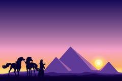 Grandes pirâmides de Egito com as silhuetas do beduíno e dos cavalos em sóis Fotografia de Stock