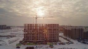 Grandes prédios de apartamentos sob a construção em um dia de inverno no por do sol Fotografia de Stock