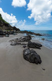 Grandes rochas na areia que conduz ao mar fotos de stock