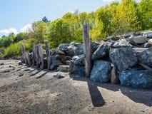 Grandes roches empilées au mur de soutènement de forme sur la plage Photographie stock libre de droits