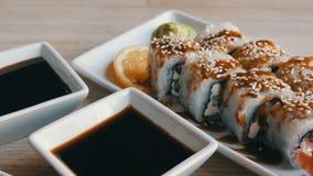 Grandes rolos de sushi brancos bonitos com wasabi do gengibre do queijo de Philadelphfia do pepino da enguia e uma fatia de limão filme