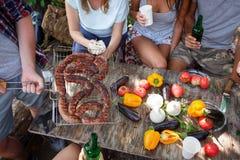 Grandes saucisses appétissantes, grillées Les amis mangent les saucisses frites dehors Vacances d'été avec des amis Photo libre de droits