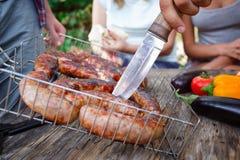 Grandes saucisses appétissantes, grillées Les amis mangent les saucisses frites dehors Vacances d'été avec des amis Image libre de droits