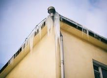 Grandes sincelos que penduram do telhado Fotografia de Stock