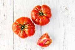 Grandes tomates fraîches rouges entières et divisées en deux sur la vieille table en bois dedans Photographie stock libre de droits