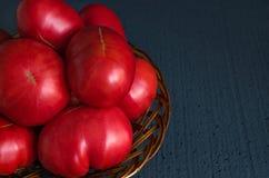 Grandes tomates juteuses dans un panier en bois sur un fond noir Images stock