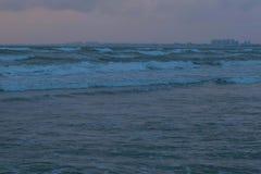 Grandes vagues de mousse de tempête en mer au coucher du soleil le soir foncé dans l'obscurité Ville côtière sur le fond photo libre de droits