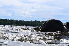 Grandes vagues venteuses éclaboussant au-dessus des roches Éclaboussure de vague dans le lac contre la plage Vagues se cassant su Images libres de droits