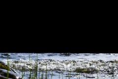 Grandes vagues venteuses éclaboussant au-dessus des roches Ondulez l'éclaboussure dans le lac d'isolement sur le fond noir Vagues Images libres de droits