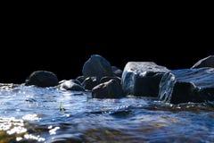 Grandes vagues venteuses éclaboussant au-dessus des roches Ondulez l'éclaboussure dans le lac d'isolement sur le fond noir Vagues Photos stock