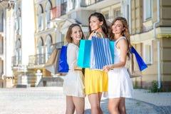 Grandes ventes Trois filles tenant les paniers et la promenade autour du Images stock