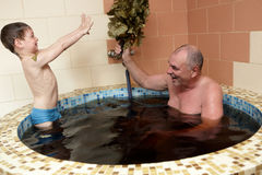 Grandfaher with grandson playing in jacuzzi Royalty Free Stock Photography