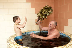 Grandfaher and grandson playing in jacuzzi Royalty Free Stock Images