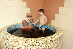 Grandfaher and grandson resting in jacuzzi Stock Image