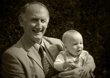 Grandfather. Holding his grandson portrait in garden Stock Image
