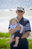 Grandfather. Outside holding a sleepy grandson at the beach Royalty Free Stock Photos