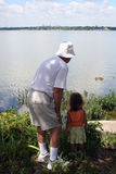 Grandfather. Young girl with grandfather at the lake. Main focus is on people, room left for text Stock Images