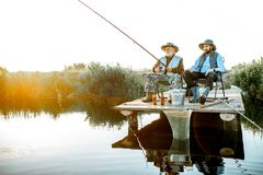 Grandfather with adult son fishing on the lake. Grandfather with adult son fishing together on the wooden pier during the morning light. View from the side of royalty free stock images