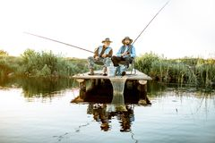 Grandfather with adult son fishing on the lake. Grandfather with adult son fishing together on the wooden pier during the morning light. View from the side of royalty free stock photography