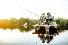 Grandfather with adult son fishing on the lake. Grandfather with adult son fishing together on the wooden pier during the morning light. View from the side of royalty free stock photo
