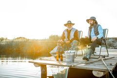 Grandfather with adult son fishing on the lake. Grandfather with adult son fishing together on the wooden pier during the morning light. View from the side of stock image