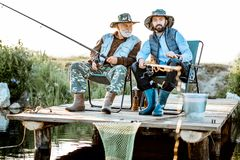 Grandfather with adult son fishing on the lake. Grandfather with adult son fishing together on the wooden pier during the morning light. View from the side of royalty free stock image
