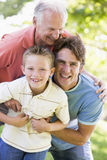 Grandfather with adult son and grandchild in park Stock Photography