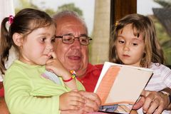 Grandfather And Granddaughters Reading Together Royalty Free Stock Photo