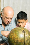 Grandfather And Grandson Look At A Globe Stock Images