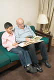 Grandfather And Grandson Sit On Couch - Vertical Royalty Free Stock Image