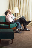 Grandfather And Grandson Sitting On Couch Reading Stock Photos
