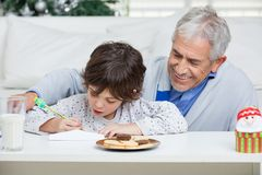 Grandfather Assisting Boy In Writing Letter To Royalty Free Stock Image