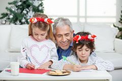 Grandfather Assisting Children In Writing Letters Stock Image