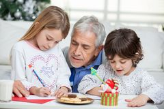 Grandfather Assisting Children In Writing Letters Stock Photo
