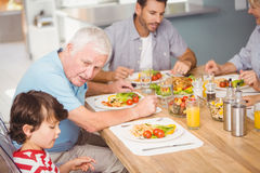 Grandfather assisting grandson while having breakfast Royalty Free Stock Image
