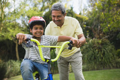 Grandfather assisting grandson while riding bicycle. At park royalty free stock photos